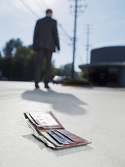 Businessman dropping wallet on sidewalk