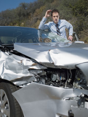 Businessman viewing damaged car front-end