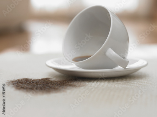 Cup of coffee spilling on carpet