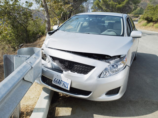 Car wrecked on road guardrail