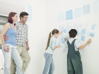Parents watching kids paint handprints on wall