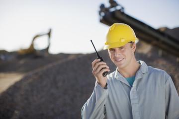 Construction worker talking into walkie-talkie