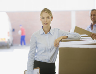 Businesswoman leaning on cardboard box