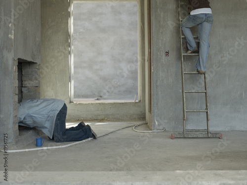 Man in chimney and woman on ladder in house under construction