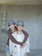 Couple in hard-hats hugging in house under construction