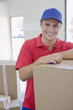 Delivery man leaning on cardboard box in warehouse
