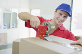 Delivery man taping cardboard box in warehouse