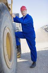 Construction worker climbing into bulldozer