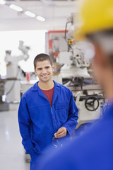 Worker in coveralls smiling in laboratory