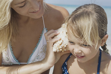 Mother holding shell up to daughter?s ear on beach