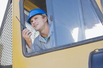 Construction worker in bulldozer talking on walkie-talkie