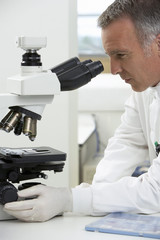 Scientist using microscope in laboratory