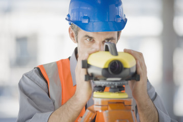 Surveyor in hard-hat using surveying equipment