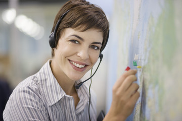 Businesswoman talking on headset in office and marking map