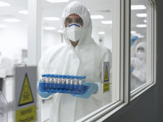 Scientist in protective clothing carrying test tubes in laboratory