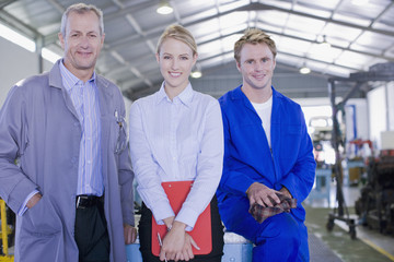 Business people and construction worker in warehouse