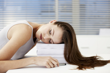 Businesswoman sleeping on stack of papers