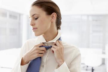 Businesswoman loosening tie