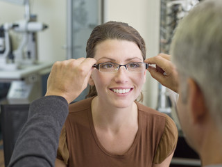 Woman trying on glasses in optometrist?s shop