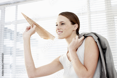 Businesswoman holding paper airplane