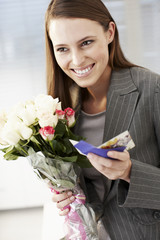 Businesswoman holding bouquet of flowers and card