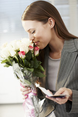 Businesswoman smelling bouquet of flowers and holding card