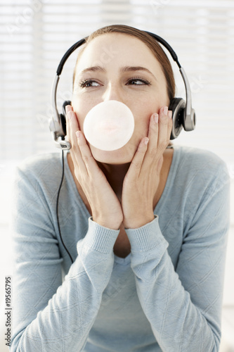 Woman wearing headset and blowing bubble