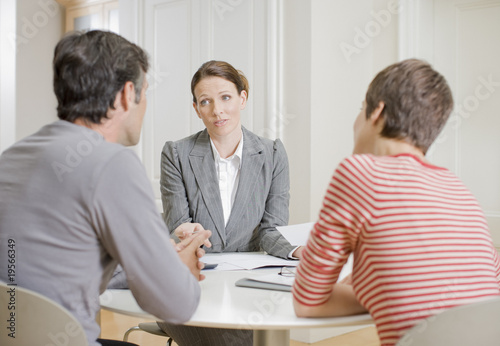 Businesswoman talking with husband and wife