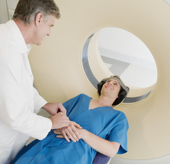 Technician preparing patient  for MRI examination