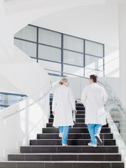 Doctors walking up staircase in hospital