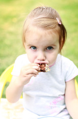 Child girl eating pastry food outdoor