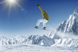 Jumping Snowboarder in alpine mountains