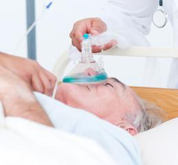 Senior patient receiving oxygen mask