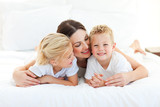 Cute children and their mom having fun lying on a bed