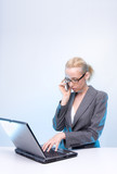 blonde businesswoman using laptop computer and mobile phone  at poster