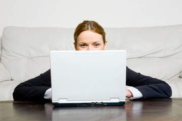 Young businesswoman behind laptop at the table