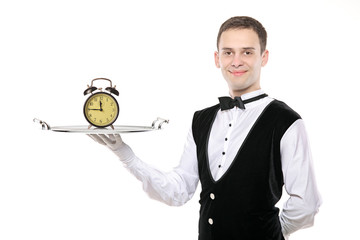 A butler holding a silver tray with an alarm clock on it