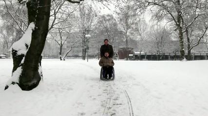 junger Rollstuhlfahrer mit Pfleger im Park