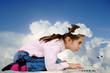 bambina al computer con la testa fra le nuvole