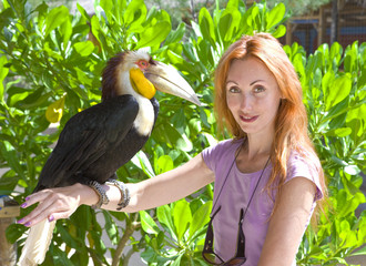 Portrait of young woman with bird toucan