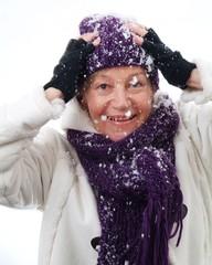 Eine Frau hat Spass im Schnee und ist beschneit.