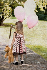 Child dragging a teddy and carrying a bunch of balloons.