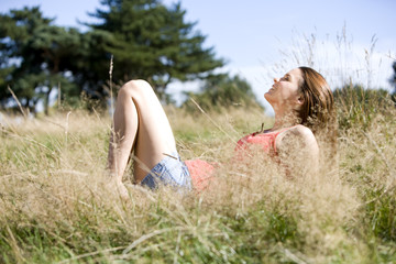 A young woman lying on the grass, enjoying the sunshine