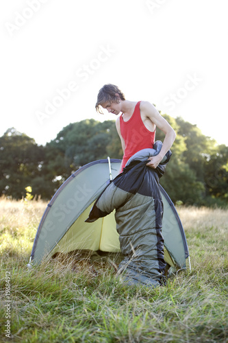 A young man standing in a sleeping bag in front of a tent