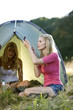 Two young women camping, one applying make-up