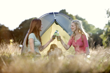 Three young women camping, two drinking beers