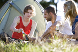 Three young people sitting in front of a tent, drinking beer