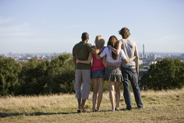 Four friends in a park looking across the city, rear view