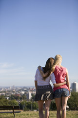 Two young women looking across the city, rear view