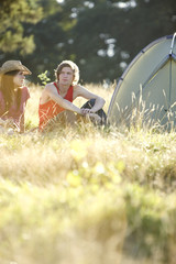 A young couple sitting in a field next to a tent